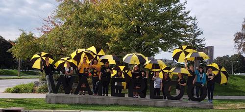 volunteers with umbrellas at Waterloo sign