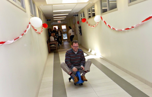 Employee racing down hallway on plasma car