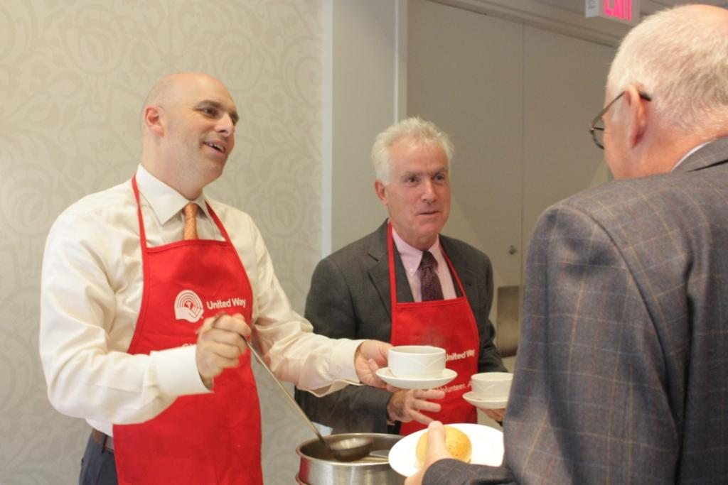 Tim Jackson and Ken McGillivray dressed in red United Way aprons serve up soup to a community member