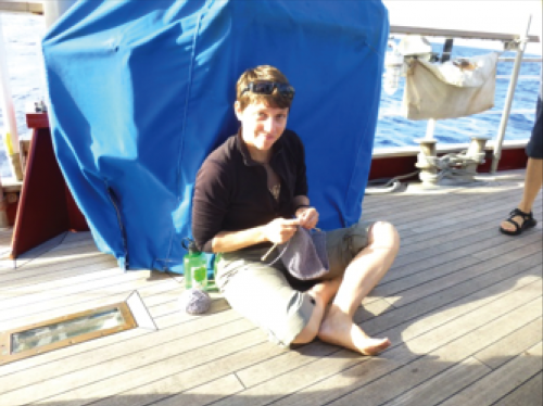 Person knitting on the quarter-deck.
