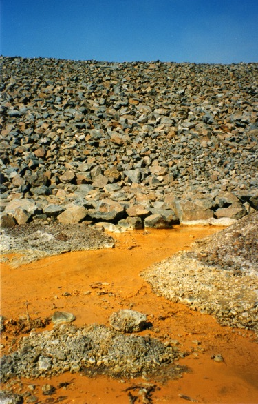 Mine effluent discharging from the bottom of a waste rock pile
