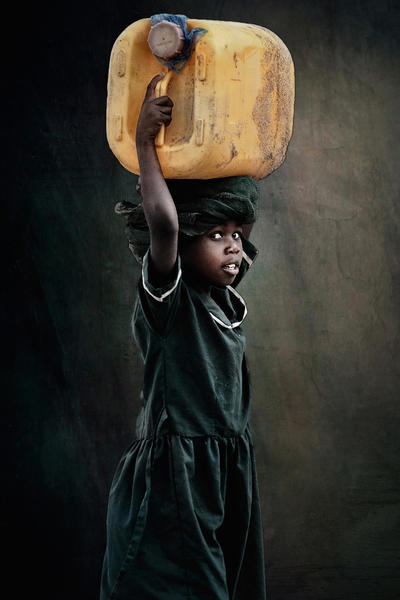 African child carries water on head