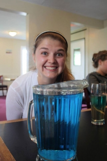 smiling student above pitcher of blue liquid.
