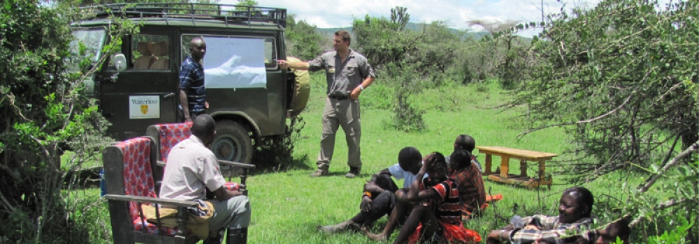 Student describing image on side of UW Jeep to local Kenyans