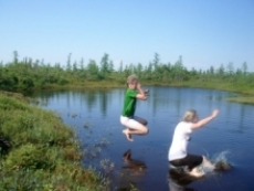 Two students jumping into a peatland pool.