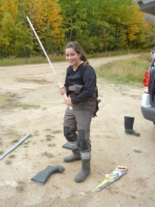 A woman holding a long stick wearing hip waders.