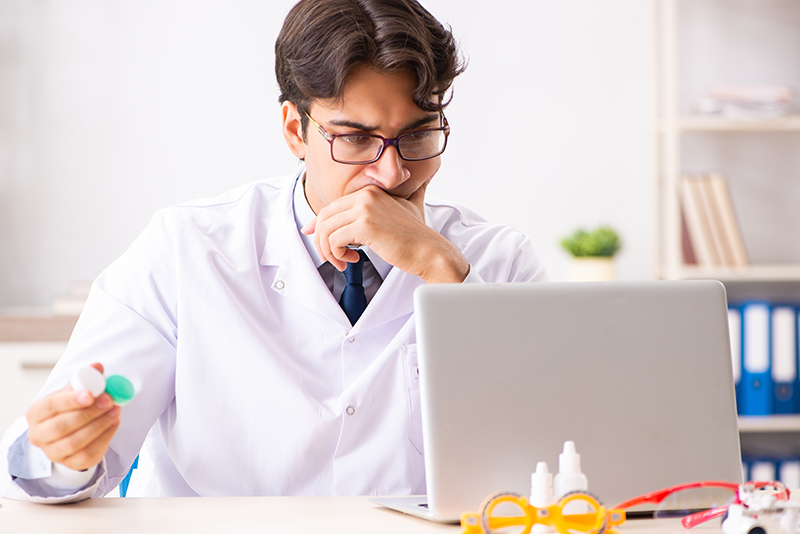 Optometrist holds a contact lens case as he looks at a laptop