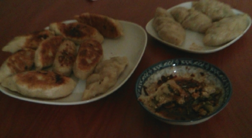 A plate of pan fried dumplings and a plate of steamed dumplings with a small plate of mix spicy suaces!
