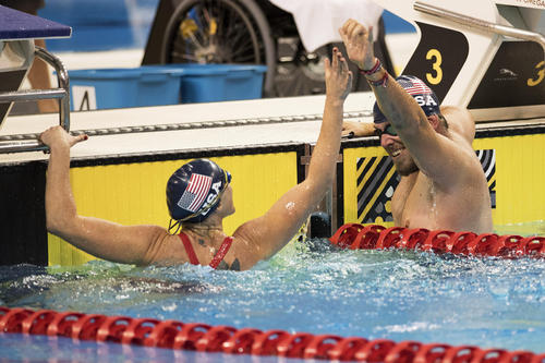 Swimmers high fiving in the pool