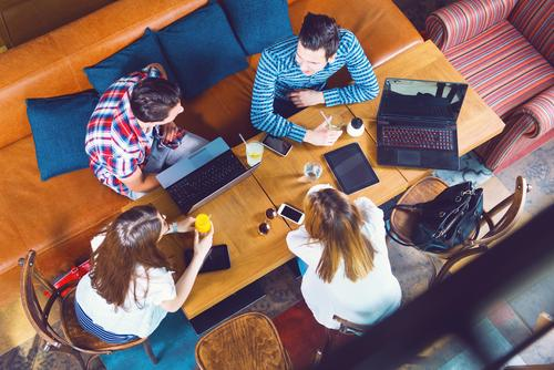 iMAGE OF A GROUP WITH LAPTOPS SITTING AROUND A TABLE IN A CAFE