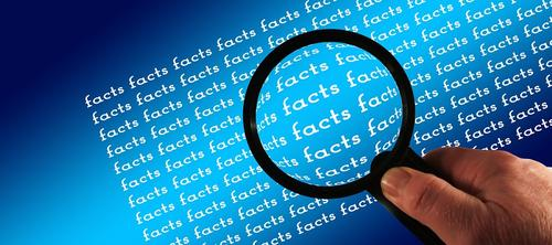 "Hand holding magnifying glass over the word ""facts"""