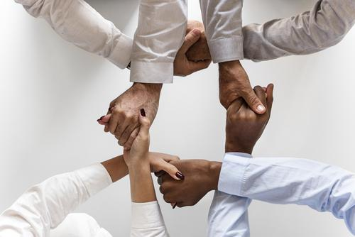 Four people holding hands, supporting one another