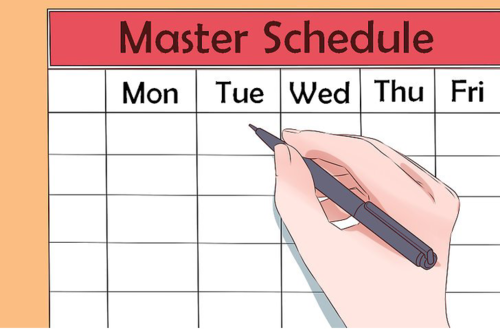 Hand holding pen positioned over a master schedule