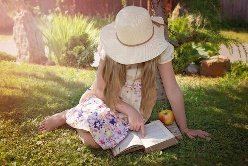 Girl sitting on grass and reading a book in the sun