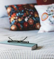Book and pair of glasses on a bed
