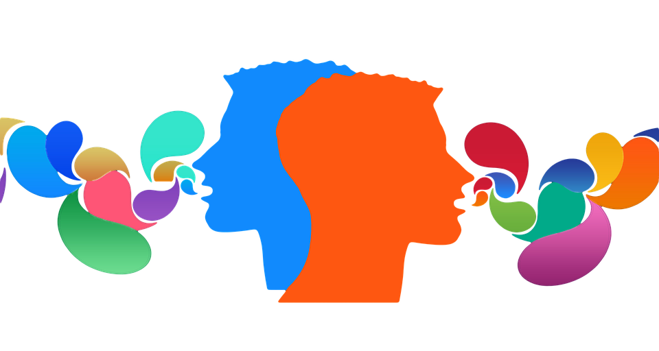 Picture of two heads facing opposite directions with colors coming out of their mouths to symbolize communication and ideas.