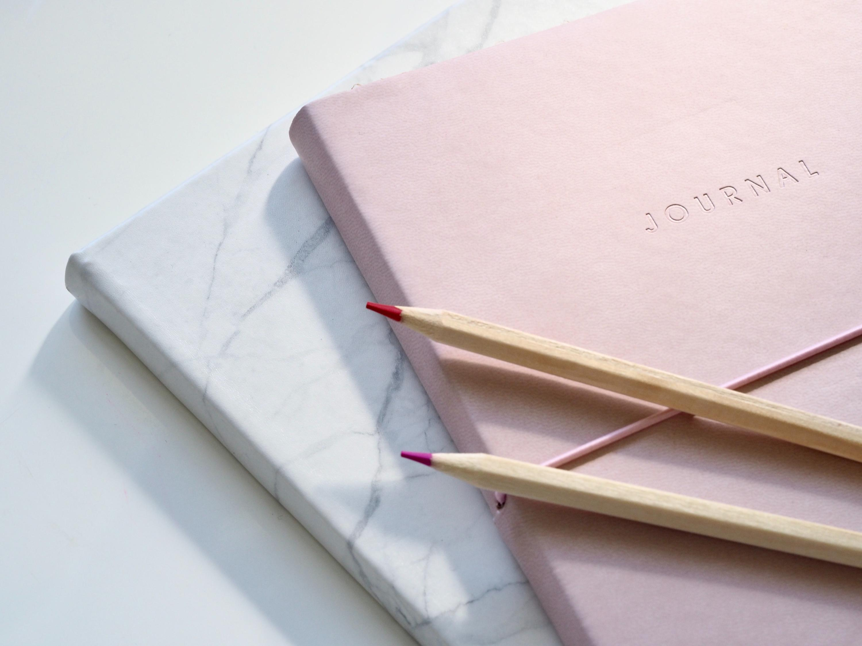Two journals and two pencils on a white desk.