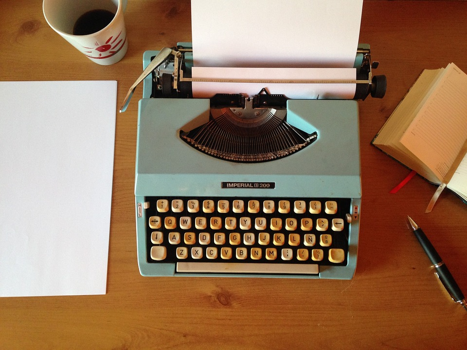 An blue typewriter sits on a wooden desk. A paper and a cup of coffee are also pictured to the left of the typewriter.