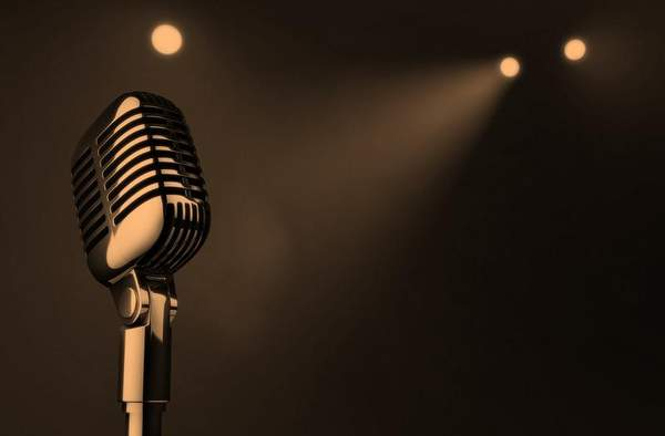 A sepia picture of an old style mic on a dark background with 3 spotlights