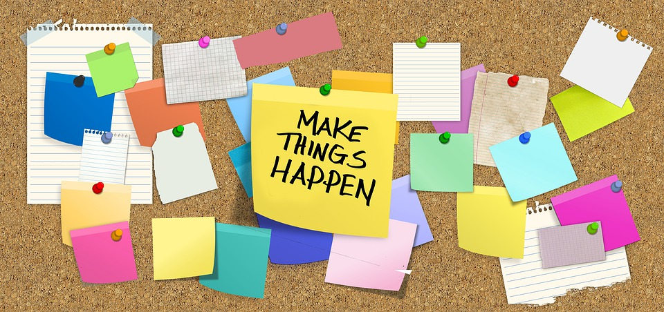 "Colourful post-it notes decorate a cork board. The center post-it says ""Make things happen"" in capital letters."